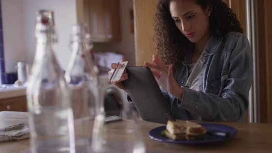 Thumbnail for Charming young latino woman making online payment with a tablet