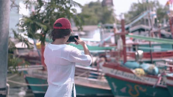 Woman Tourist Shoots Pictorial Bay with Boats on Cell Phone