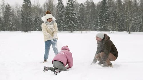 Family Throwing Snow in Park