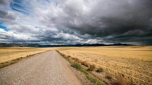 Time lapse of road through rolling hills of cut straw with moody sky