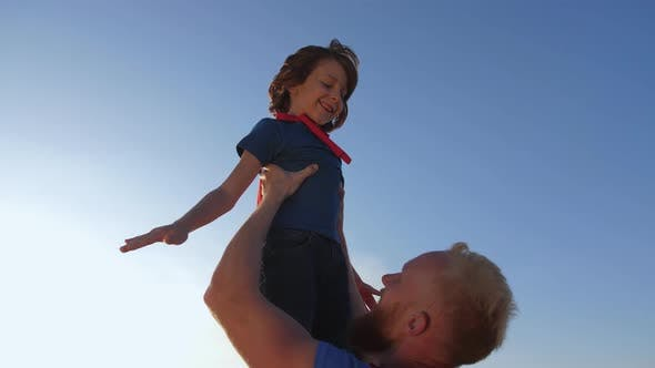 Thumbnail for Dad Raising Son High Imitating Superhero's Flight