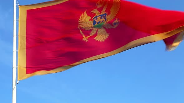 Thumbnail for Waving national flag of Montenegro on a pole - red and yellow against clear blue sky on a sunny day.