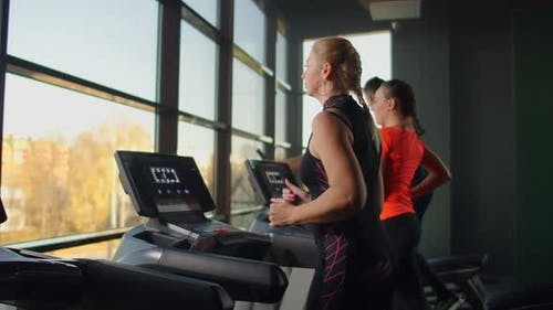 A Young Beautiful Woman and Three People Running on a Treadmill in a Fitness Room Performing a
