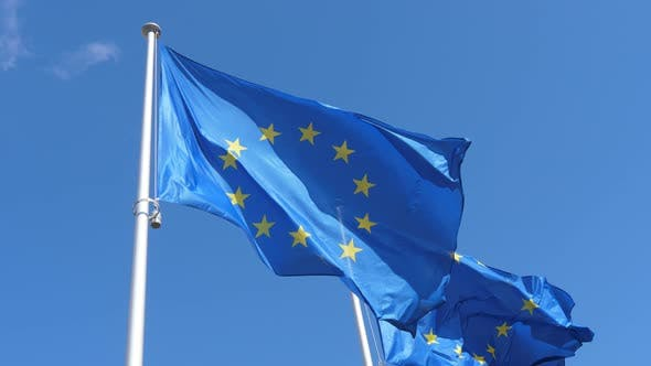 Cover Image for Two EU Flags Waving Freely on Flagpole in Celeste Sky in Spring in Slow Motion