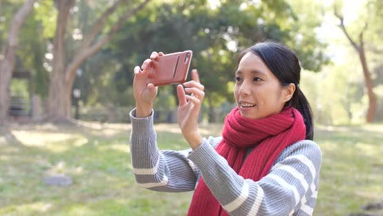Thumbnail for Woman using cellphone for taking photo in park