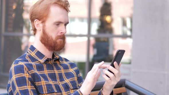 Cover Image for Beard Young Man Using Smartphone while Sitting Outdoor