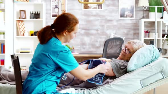 Thumbnail for Nurse Measuring Blood Pressure of Old Sick Lady Laying in Hospital Bed