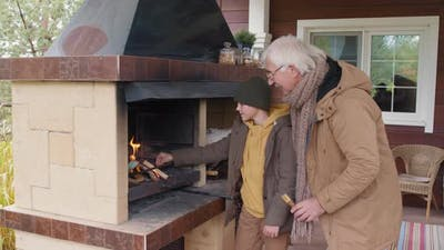 Grandfather and Child Kindling Outdoor Fireplace