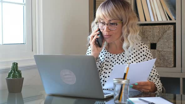 Woman at work in home office speaking and explaining job with smart phone and laptop  computer
