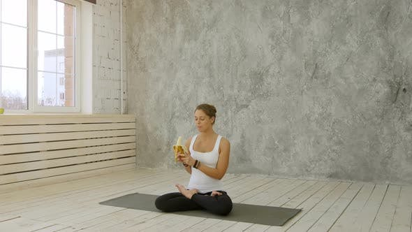 Thumbnail for Cute Young Woman Chewing a Banana While Sitting on Exercise Mat