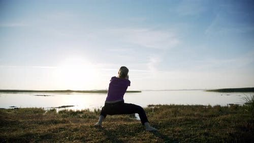 Silhouette of Young Sporty Woman Engaged in Gymnastics on Background Sky and Lake. V4