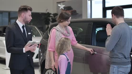 Thumbnail for Young Caucasian Family Selecting New Automobile in Car Showroom. Man, Woman and Little Cute Girl