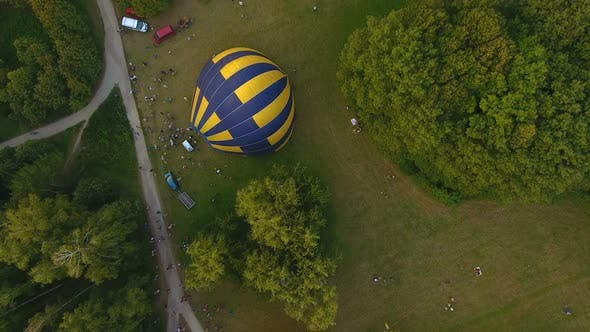 Thumbnail for Several Air Balloons Lying on Ground and Getting Inflated Surrounded by Crowd