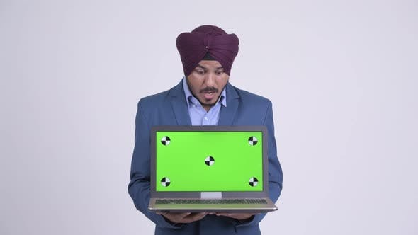 Thumbnail for Happy Indian Sikh Businessman Showing Laptop and Looking Surprised