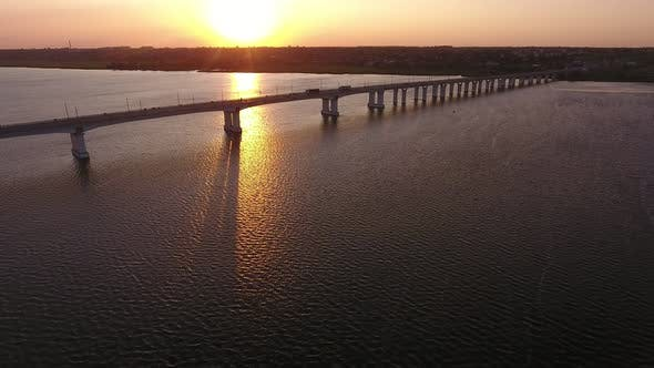 Thumbnail for Aerial Shot of a Beautiful River Bridge Over the Dnipro with a Golden Sun Path