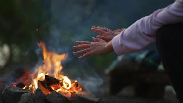 Hands warming at a campfire