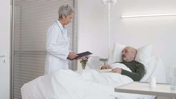 Female Doctor Coming to Check on Aged Patient