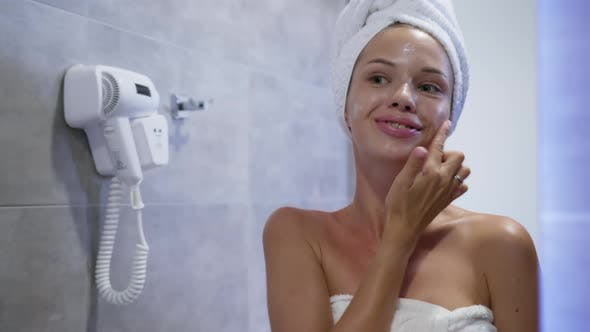 Thumbnail for Young Girl in Towel Smears Her Face with Cream in Bathroom