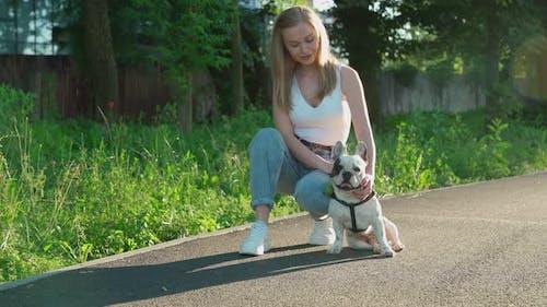 Junge Frau Streicheln Französisch Bulldogge im Park.