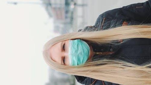 Coronavirus Pandemic: Blonde Woman in a Medical Mask Walking Down the Street