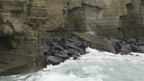 Powerful waves hitting rocky cliffs and falling to produce froth and splashes