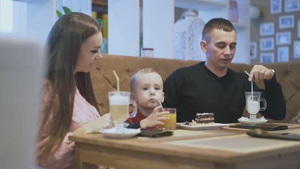 Mutter und Vater Blick auf Sohn trinken Orangensaft