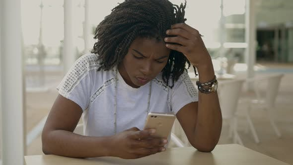Thumbnail for Thoughtful African American Woman Using Smartphone