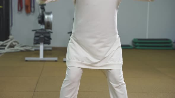 Muslim Woman in a Hijab Does Squats in an Indoor Gym