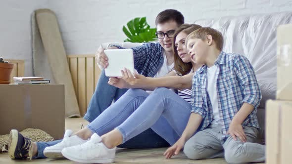 Cover Image for Young Family Taking Pictures on Tablet