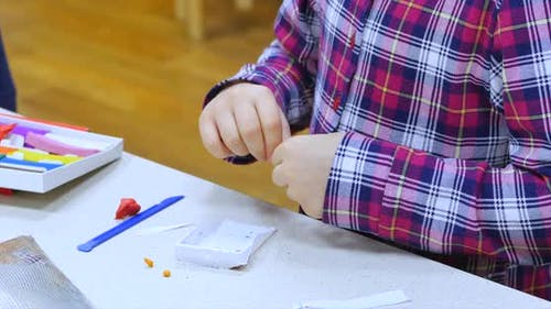 Young Female Child or Girl Artist in an Art Workshop, Sits at a Table and Sculpts From on Plasticine