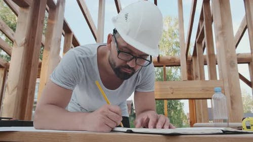 Builder-engineer Makes Notes in the Log of Work at Construction Site