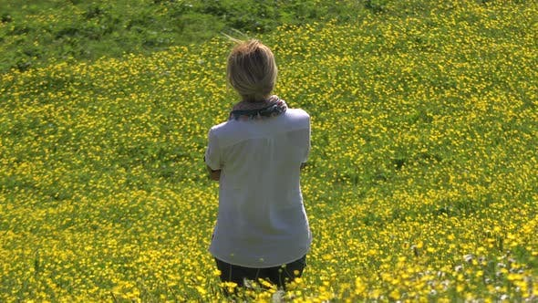 Blond Haired Alone Woman is Watching View in Yellow Flowery Meadow