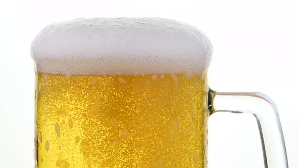 Pouring lager beer with bubbles and froth over the top in glass mug over white background