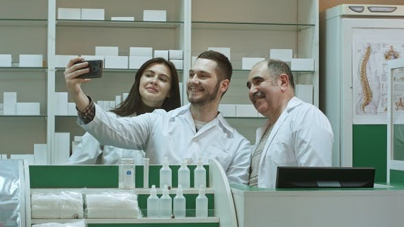 Cheerful team of pharmacist and interns take selfie via