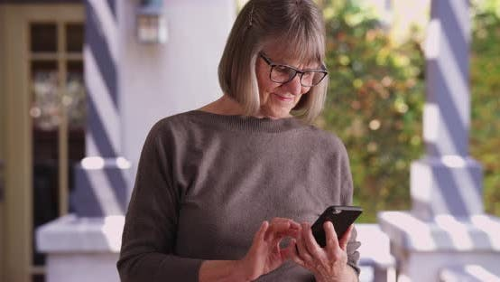 Thumbnail for Happy senior woman sending text message on phone outside in the daytime