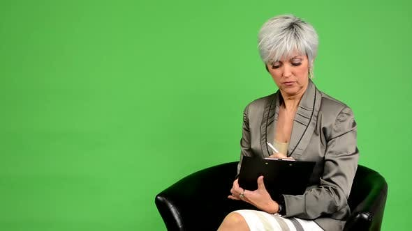 Thumbnail for Business Middle Aged Woman Sits and Writes To Paper and Smiles - Green Screen - Studio