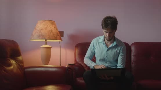Businessman uses laptop sitting on the sofa
