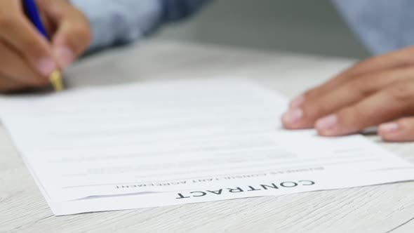Close-up Businessman Putting Signature on Paper. Signs a Contract. Successful Deal, Negotiations.