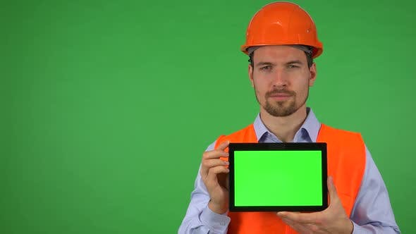 Thumbnail for A Young Construction Worker Shows a Tablet with Green Screen To the Camera - Green Screen Studio