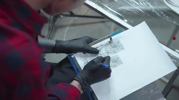 Woman in Latex Gloves Draws a Sketch of a Tattoo
