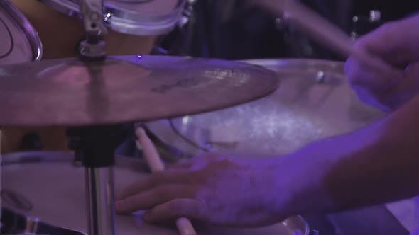 Drummer Plays Percussion Instruments at a Concert As Part of a Musical Group