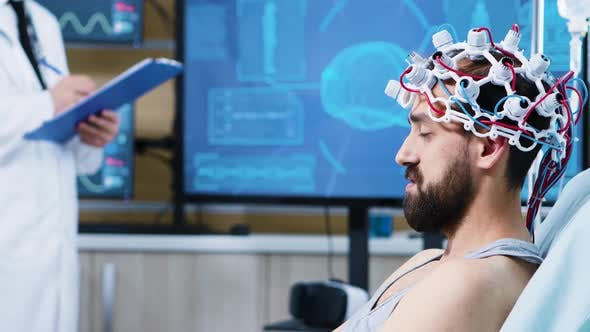 Patient with Brainwaves Scanning Headset Sitting on Bed