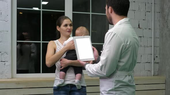 Thumbnail for Doctor Holding a Tablet Computer Talking To Mother and Her Child