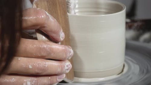 Moulding a clay pot on wheel