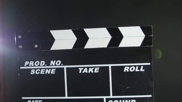 Thumbnail for Hands Holding a Film Clapper Board, on Black, Close Up, Back Light