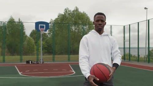 Porträt des Schwarzen Mannes mit Basketball draußen