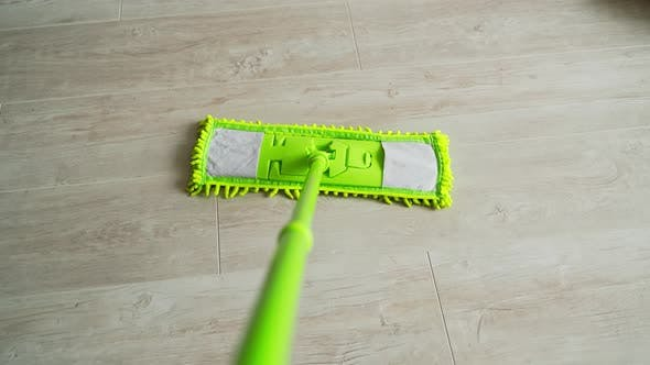 Green microfiber mop moving on the parquet floor to keep the house clean