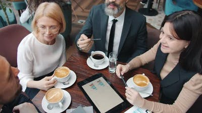 Zoom-out of Group of Businesspeople Discussing Project in Cafe Looking at Tablet Screen