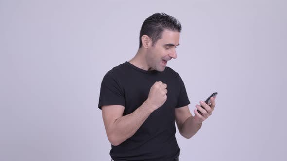 Thumbnail for Happy Handsome Man Using Phone and Getting Good News