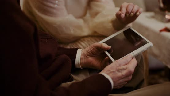 Cover Image for Granddaughter And Grandfather Discussing Over Digital Tablet At Home